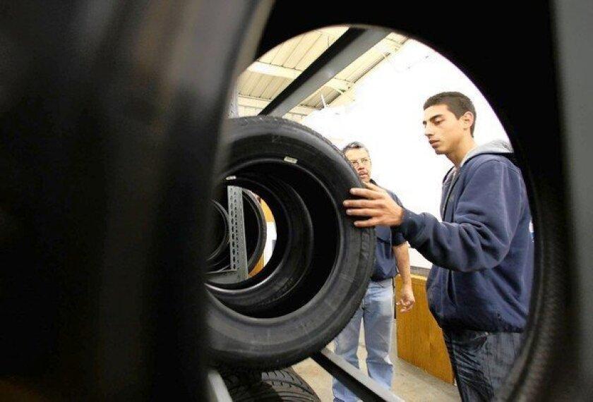 Salesman Jorge Fernandez, left, stands by as Jesse Godinez of San Fernando checks out tires at a Rent-a-Wheel store in Canoga Park.