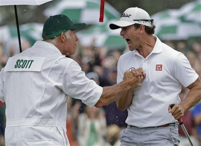 Adam Scott, of Australia, celebrates with his caddie Steve Williams after a birdie putt on the 18th green during the fourth round of the Masters golf tournament Sunday, April 14, 2013, in Augusta, Ga. (AP Photo/David J. Phillip)