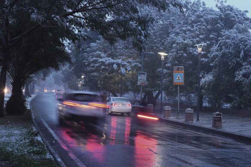 Fresh snow falls while motorists drive through Abu Nawas street in central Baghdad, Iraq, Tuesday, Feb. 11, 2020. Snow fell across the Iraqi capital Baghdad for the first time in a decade on Tuesday as morning temperatures uncharacteristically hovered around freezing. (AP Photo/Hadi Mizban)