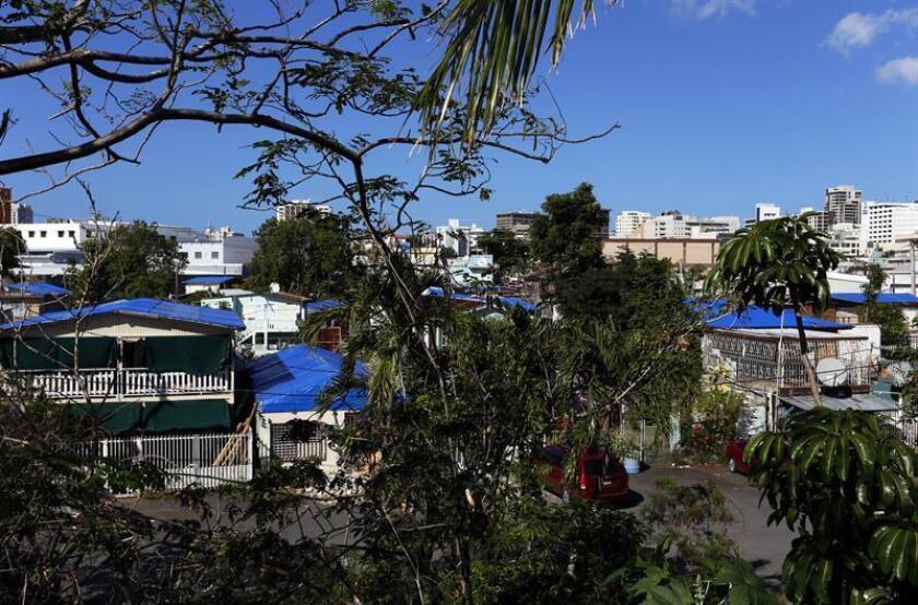Fotografía donde se muestran los techos de las casas afectadas por el paso de los huracanes Irma y María cubiertos con toldos en el barrio Santurce del municipio de San Juan, Puerto Rico. EFE/Archivo