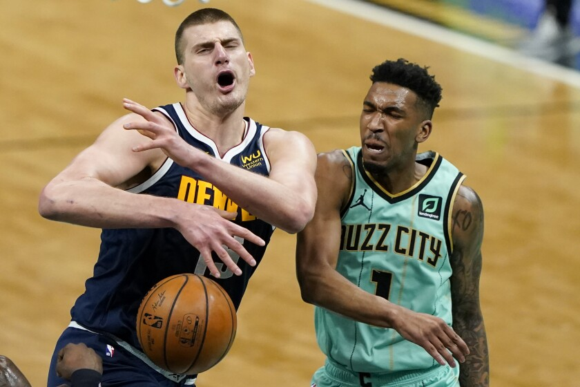 Denver Nuggets center Nikola Jokic, left, is fouled by Charlotte Hornets guard Malik Monk during the first half of an NBA basketball game on Tuesday, May 11, 2021, in Charlotte, N.C. (AP Photo/Chris Carlson)