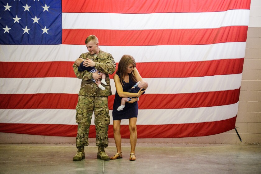 Spc. Aaron Schade and his wife, Amanda, prepare to be photographed with their twin boys upon his return to North Carolina from Afghanistan in July 2014.