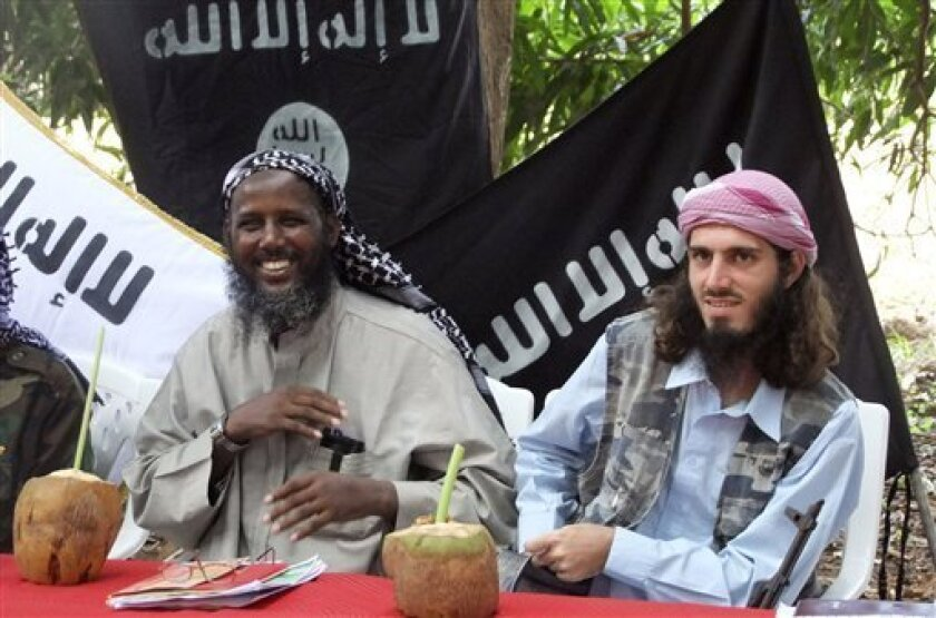 """FILE - In this Wednesday, May 11, 2011 file photo, American-born Islamist militant Omar Hammami, 27, also known as Abu Mansur al-Amriki, right, and deputy leader of al-Shabab Sheik Mukhtar Abu Mansur Robow, left, sit under a banner which reads """"Allah is Great"""" during a news conference of the milita"""