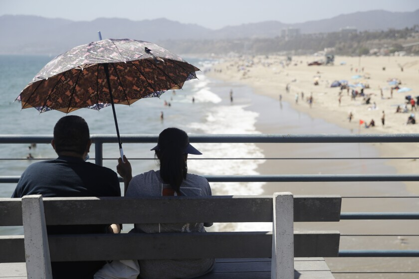 FILE - In this July 12, 2020, file photo, visitors sit on a bench on the pier amid the coronavirus pandemic in Santa Monica, Calif. California will roast in a dangerous heat wave through the Labor Day weekend and options for cooling off may be limited by coronavirus concerns at beaches and calls for energy conservation that could limit use of air conditioning at home. (AP Photo/Marcio Jose Sanchez, File)
