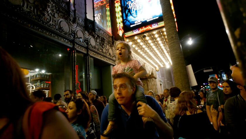 """Mariella Braniger, 2, of Ladera Ranch gets a ride on her father Robin Braniger€'s shoulders as he walks through the crowd outside the """"Beauty and the Beast"""" opening night at Hollywood's El Capitan Theatre."""