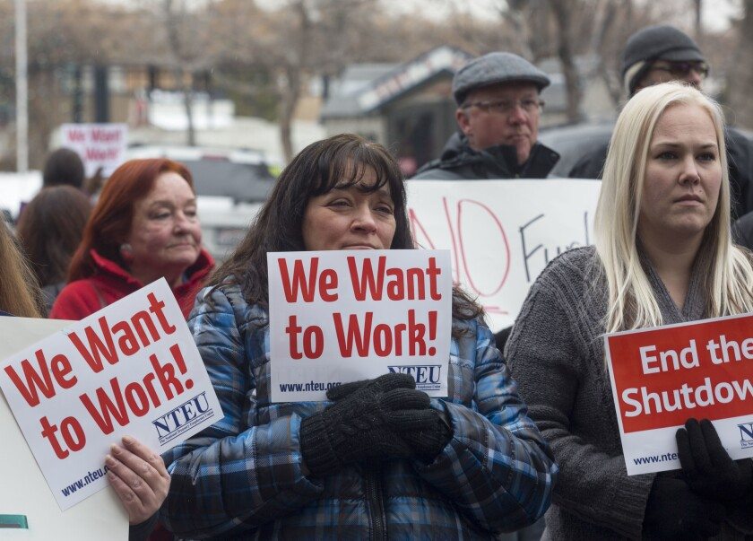 IRS employee Donna Orton, center, holds a sign protesting the government shutdown last week at the James V. Hansen Federal Building in Ogden, Utah.