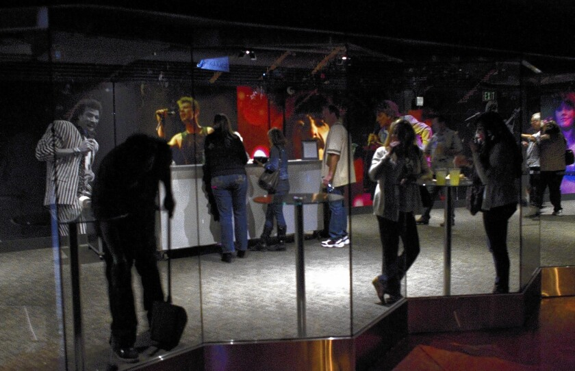 Patrons watch the opening act through glass doors as others stand in line at a floor bar during the Eagles' concert at the newly renovated Forum in Inglewood.