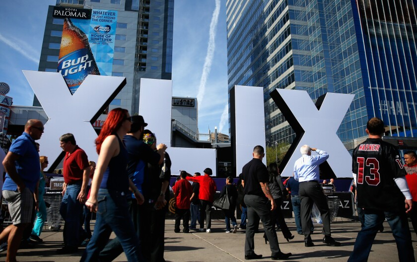 Dish Network announced a Super Bowl feature that enables customers to watch a block of commercials on Monday, the day after the game. Pictured: People in Phoenix walk past the logo for Sunday's Super Bowl XLIX.