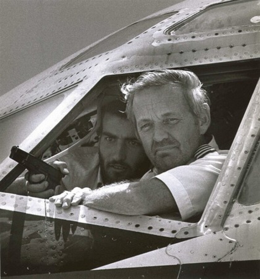 A Hezbollah militant, left, who some believe to be Imad Mughnieh, holds TWA pilot John Testrake hostage in Beirut in 1985, a hijacking he was suspected of planning.