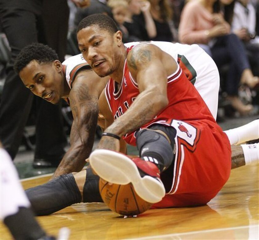 Chicago Bulls' Derrick Rose, right, goes to the floor for a loose ball against Milwaukee Bucks' Brandon Jennings, left, during the second half of an NBA basketball game on Saturday, Feb. 4, 2012, in Milwaukee. (AP Photo/Jeffrey Phelps)