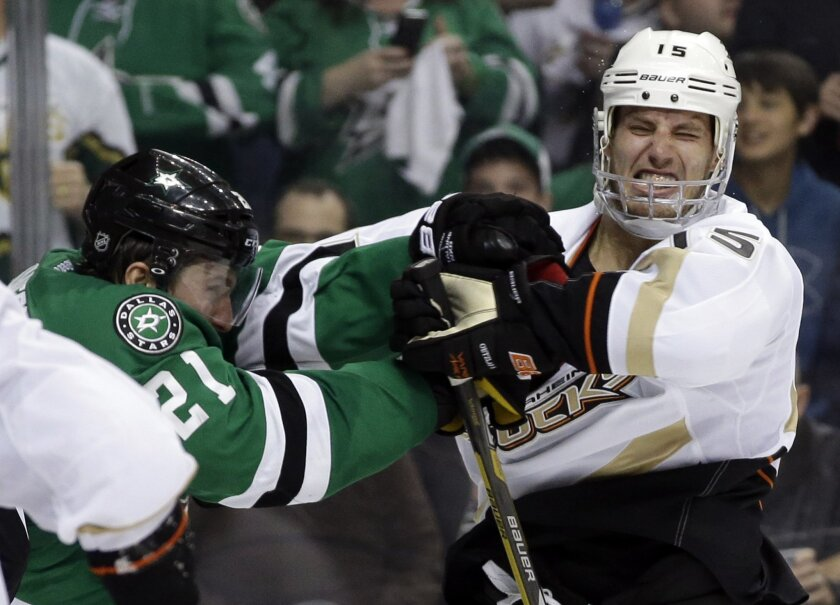 Anaheim Ducks center Ryan Getzlaf (15) recoils from a punch to the mask by Dallas Stars' Antoine Roussel (21) of France in the second period of Game 3 of a first-round NHL hockey Stanley Cup playoff series game, Monday, April 21, 2014, in Dallas. (AP Photo/Tony Gutierrez)