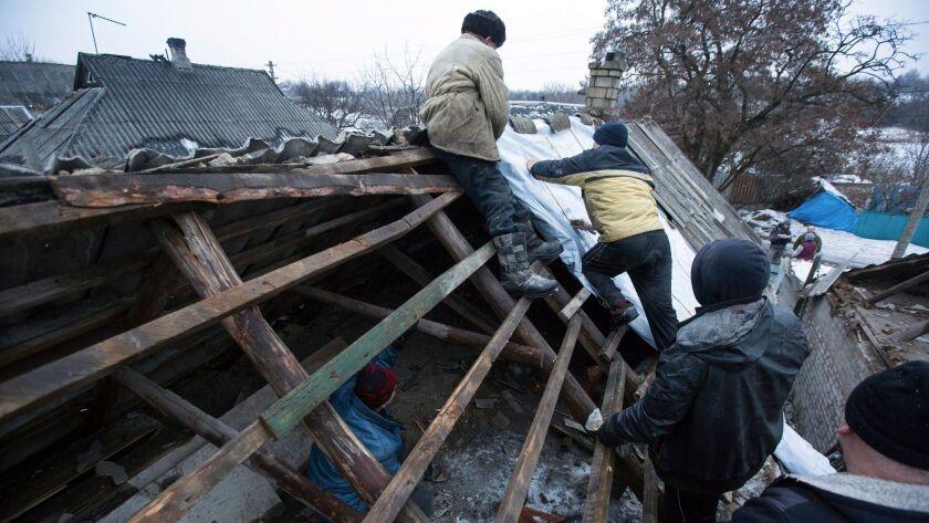Ukrainian men repair a roof damaged after shelling in Avdiivka, Donetsk.