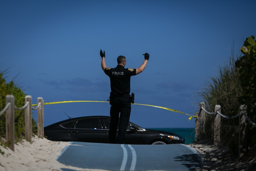 A Miami Beach police officer stands in a closed beach entrance on South Beach.