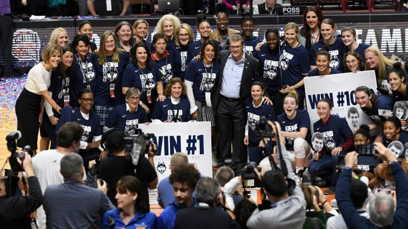 Connecticut head coach Geno Auriemma celebrates his 1,000th career victory with members of past and present players after an 88-64 win against Oklahoma on Tuesday.
