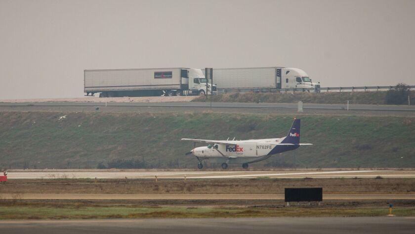 A FedEx plane taxis on the runway adjacent to Highway 99 at the Visalia Airport. Visalia Municipal A