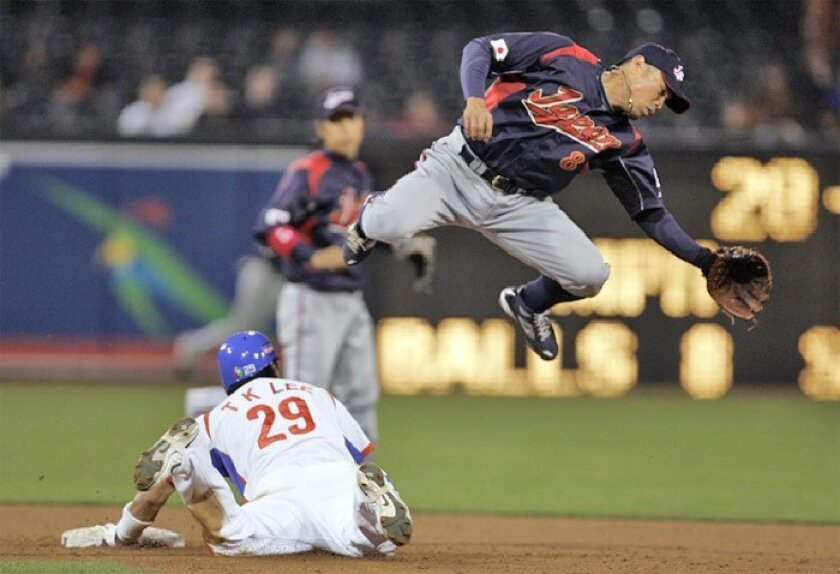 South Korea baserunner Taek Keun Lee slides safely into second under 