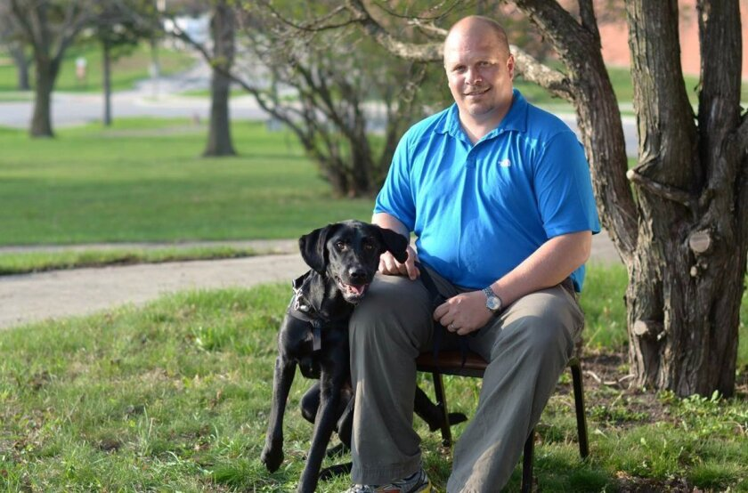 ADVANCE FOR USE SUNDAY, NOV. 8, 2015 AND THEREAFTER - In this March 2012 photo provided by Paws & Effect, Wade Allen Baker sits with Honor at the end of the PTSD service dog's placement with him and the workshop that all recipients go through at Camp Dodge in Johnston, Iowa. A year after graduation