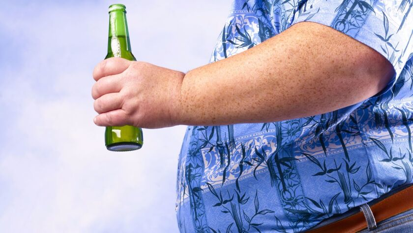 Obese man holding beer bottle against sky. Getty Images