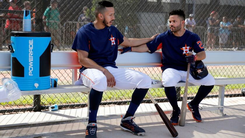 Houston Astros' Carlos Correa, left, and Jose Altuve chat in the dugout before taking batting practi