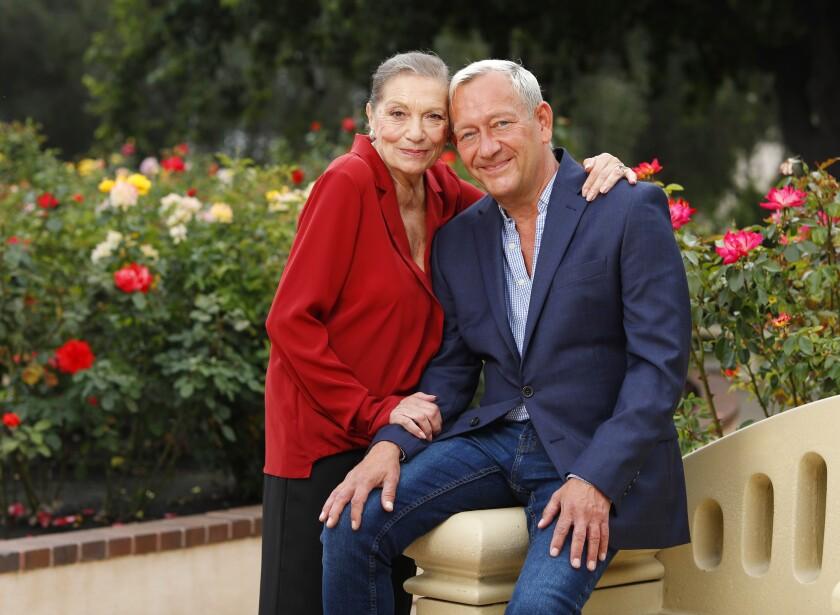 Graciela Daniele y Michael John LaChiusa se abrazan en un jardín de rosas.