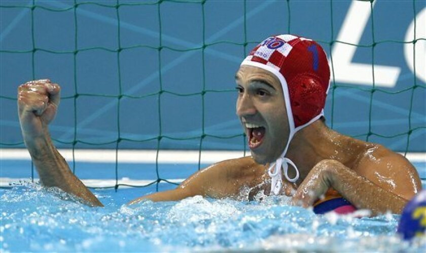 Croatia goalkeeper Josip Pavic reacts after making a save against Croatia during a men's semifinal water polo match at the 2012 Summer Olympics, Friday, Aug. 10, 2012, in London. (AP Photo/Julio Cortez)