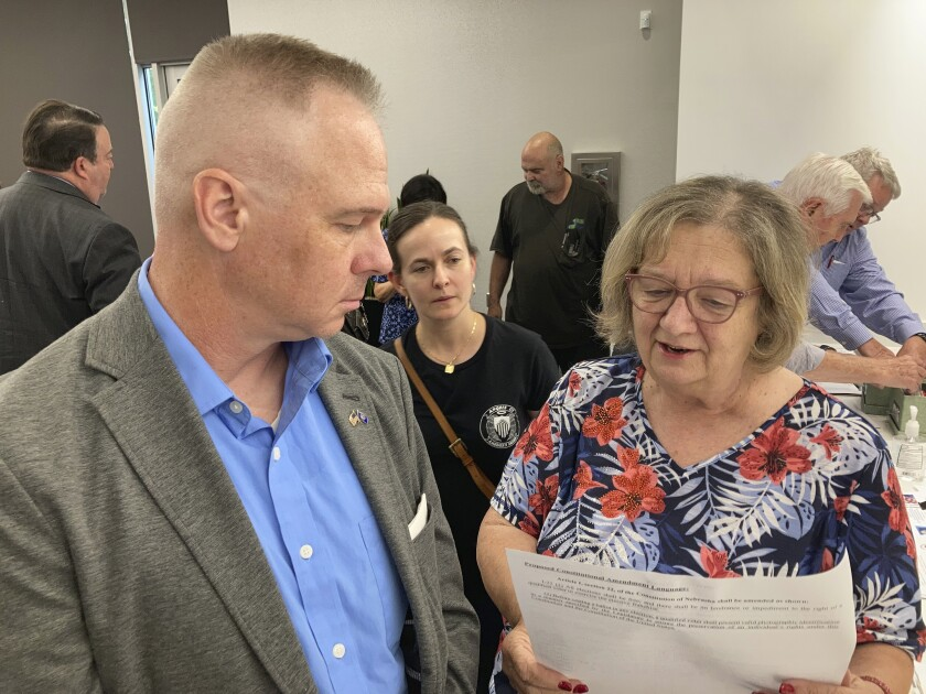 Brian Stransky, of unincorporated Sarpy County, Nebraska, listens as Citizens for Voter ID campaign official Nancy McCabe reads to him from a voter ID ballot petition on Thursday, Sept. 2, 2021, at a local Republican Party meeting in Papillion, Nebraska. Activists who want to require voters to show a government-issued identification at the polls are taking the issue directly to voters after facing years of rejection in the Nebraska Legislature. (AP Photo Grant Schulte)