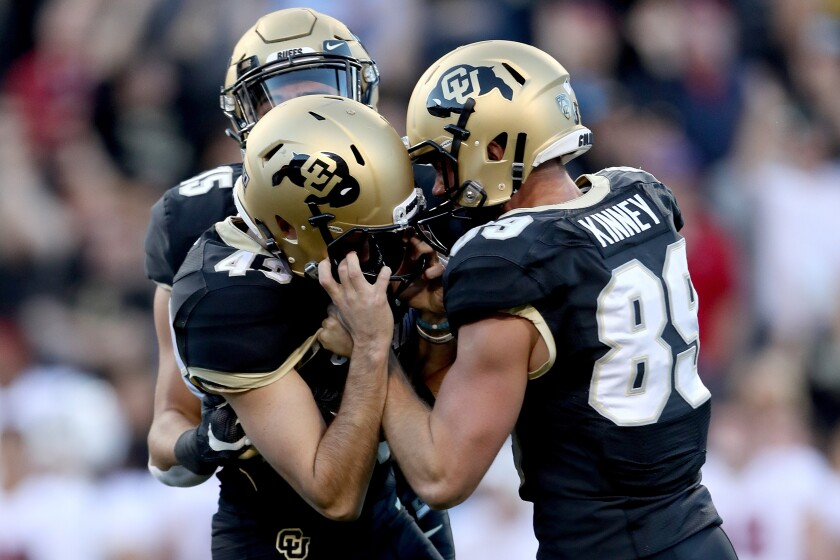 Colorado's Legend Brumbaugh (15), Alex Kinney (89) and Evan Price (43) celebrate  a game winning  field goal by Price against Stanford Cardinal in the final seconds on Saturday.