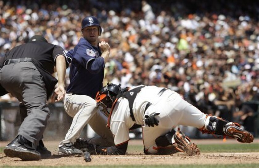 San Diego Padres' Chase Headley, center, scores past San Francisco Giants catcher Bengie Molina as home plate umpire Angel Camposs, left, leans in before making the call during the fifth inning of a baseball game Sunday, July 12, 2009, in San Francisco. Headley scored on a single by Luis Gonzalez. (AP Photo/Ben Margot)