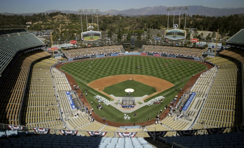FILE - In this Oct. 3, 2014, file photo, the Los Angeles Dodgers and the St. Louis Cardinals gather on the field for batting practice at Dodger Stadium before Game 1 of baseball's NL Division Series in Los Angeles. The Los Angeles Dodgers have signed a multi-year deal to book more high-end concerts