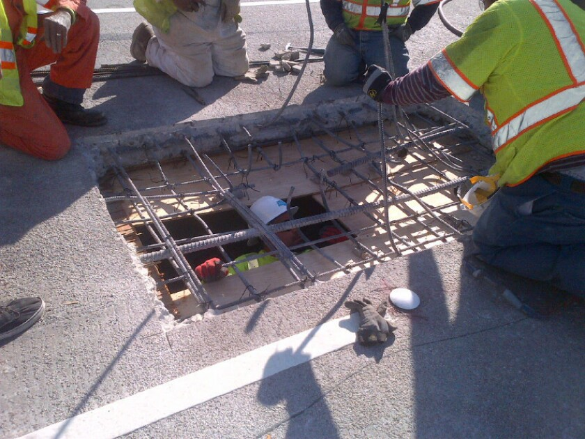 Caltrans workers repair a pothole on the 5 Freeway in Boyle Heights that developed from a patch job performed the day before to repair damage caused by an overturned big rig.