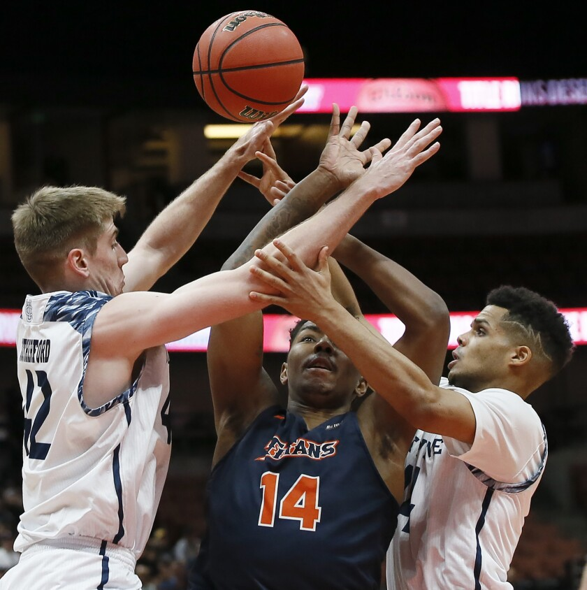 Cal State Fullerton guard Khalil Ahmad, center, battles for a loose ball against UC Irvine's Tommy Rutherford, left, and Evan Leonard during the first half of the Big West men's tournament championship in Anaheim.