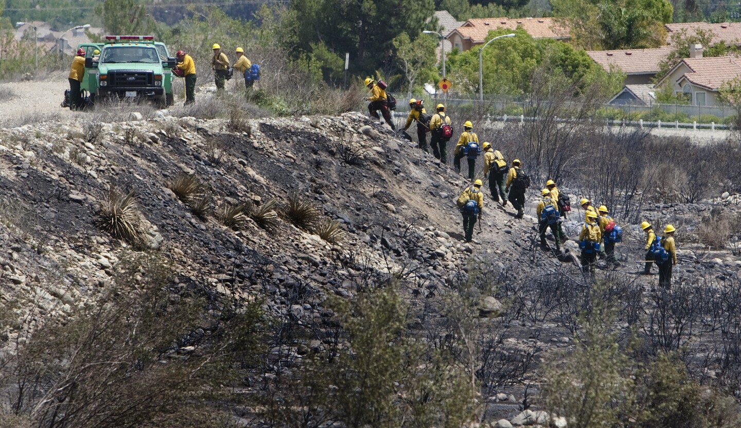 Hot shot crews traverse the burned terrain while looking for smoldering embers on the second day of the Etiwanda fire in Rancho Cucamonga.