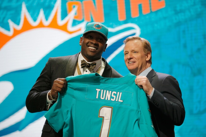 Ole Miss OT Laremy Tunsil holds up a jersey with NFL Commissioner Roger Goodell after being drafted No. 13 overall by the Miami Dolphins.