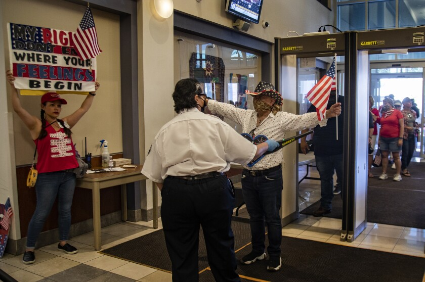 Protesters enter the County Administrative Center for a Riverside County Board of Supervisors meeting last week.