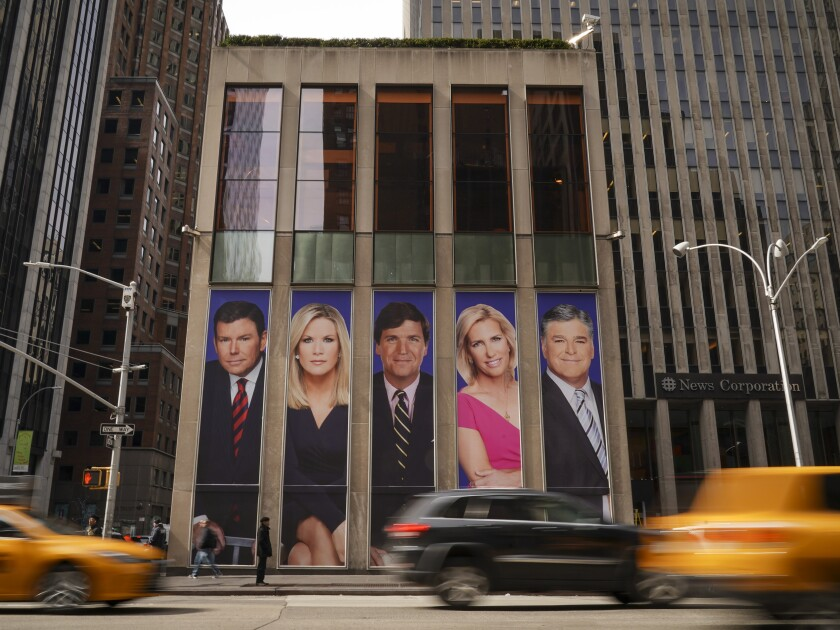 Images of Fox News personalities on the front of the News Corp. offices in New York City.