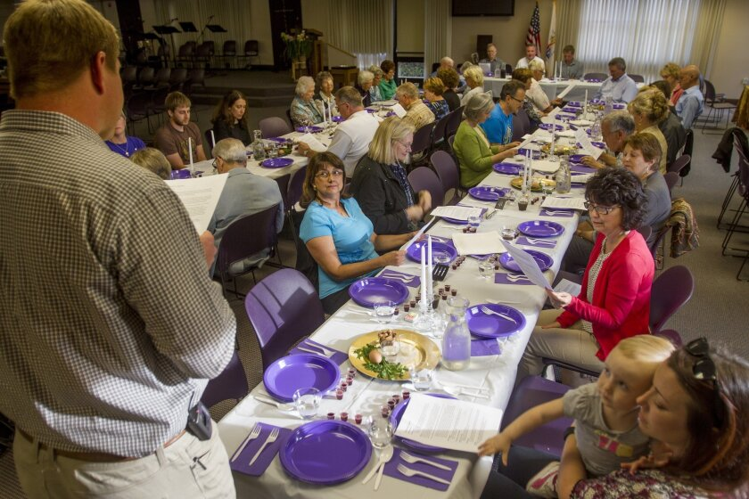 Associate Pastor Jeremiah Knabe, left, reads some of the story of Passover during a ceremonial Passover dinner at the Christ Presbyterian Church in Carlsbad Thursday. photo by Bill Wechter