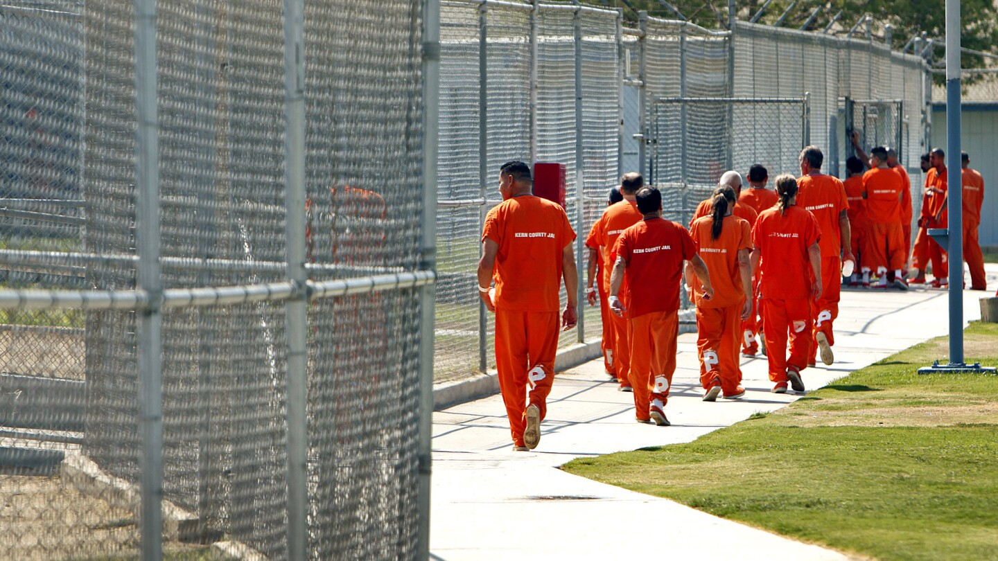 Inmates walk through the yard at the Kern County Sheriff's Department's Lerdo Detention Facility in Bakersfield. Because of the diversion of state prisoners, one Kern County jail reaches maximum capacity two or three times a week and must release 20 to 30 inmates to make room.