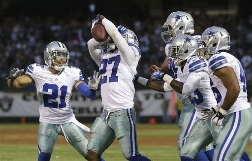 Dallas Cowboys defensive back J.J. Wilcox (27) celebrates with cornerback Sterling Moore (21) and teammates after intercepting a pass from Oakland Raiders quarterback Terrelle Pryor during the second quarter of an NFL preseason football game in Oakland, Calif., Friday, Aug. 9, 2013. (AP Photo/Marcio Jose Sanchez)