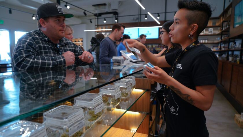 On the first day of recreational marijuana sales in San Diego, Genesiee Cervantes with Urbn Leaf assisted Billy Johnson with his selections.