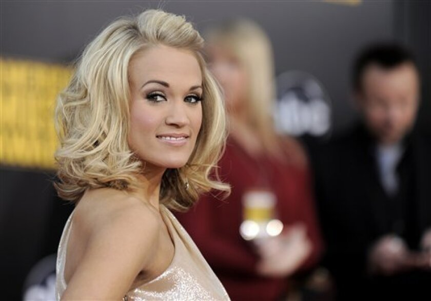 "FILE - In this Nov. 22, 2009 file photo, Carrie Underwood arrives at the 37th Annual American Music Awards in Los Angeles. The country music star hosts Monday's ""An All-Star Holiday Special"" on Fox, and believes it's just the tonic for the regular TV lineup. (AP Photo/Chris Pizzello, File)"