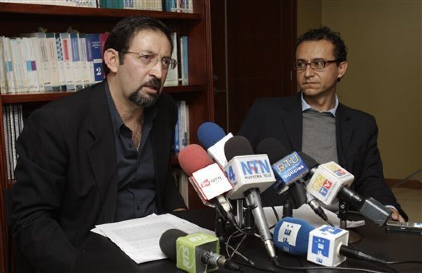 Journalists Juan Carlos Calderon , left, and Cristian Zurita announce at a news conference that they will appeal an Ecuadorean court order to pay $1 million each to President Rafael Correa, in Quito, Ecuador, Tuesday Feb. 7, 2012. The court found the pair guilty of defamation for reporting on contracts the president's brother allegedly had with the state. (AP Photo/Dolores Ochoa)
