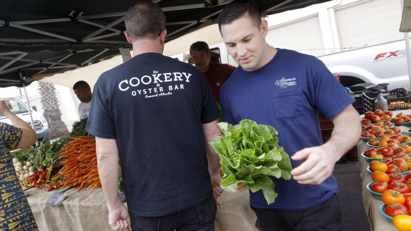 Mike Reidy (right), chef de cuisine at Ironside Fish & Oyster inspects some romaine lettuce alongside executive chef Jason McLeod at the inaugural Little Italy Wednesday Market.
