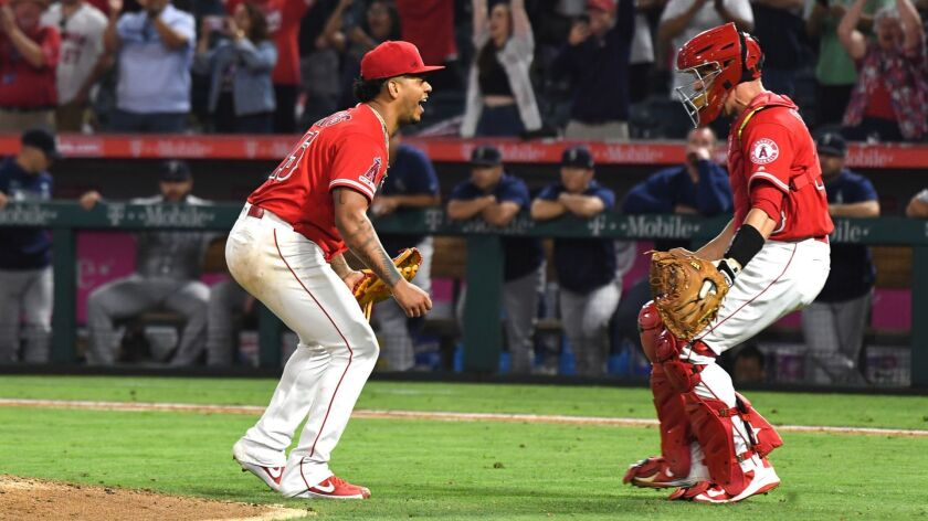 ANAHEIM, CALIFORNIA JULY 12, 2019-Angels pitcher Felix Pena celebrates with catcher Dustin Garneau a
