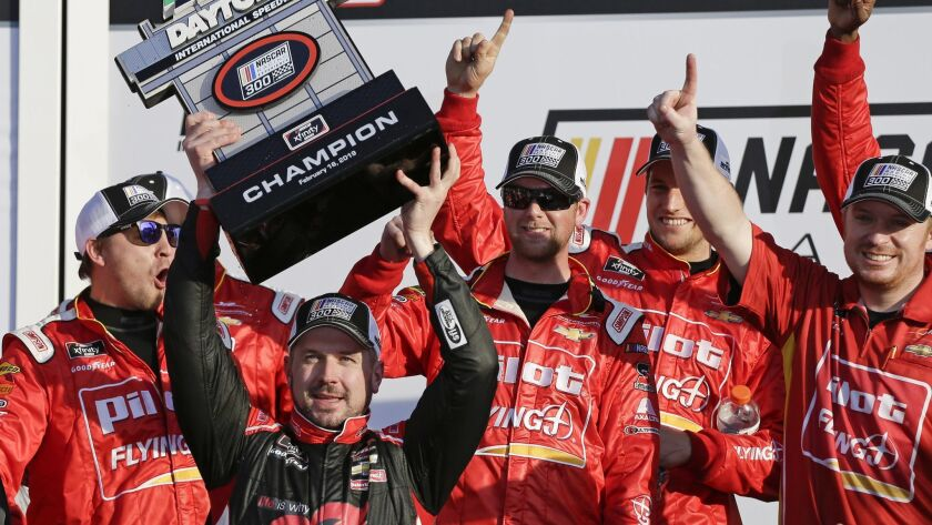 Michael Annett, front left, holds up the Championship trophy after winning the NASCAR Xfinity series