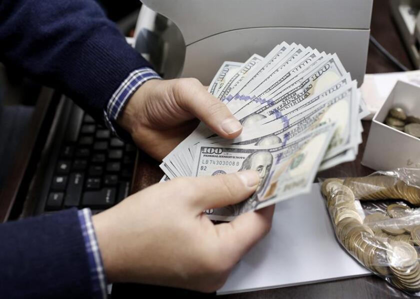 Un hombre cuenta billetes en una oficina de cambio en Ciudad de México. EFE/Archivo