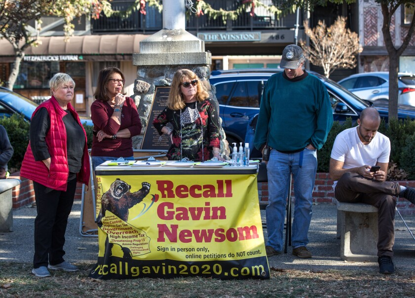 "Five people stand at a table with a banner that reads ""Recall Gavin Newsom."""