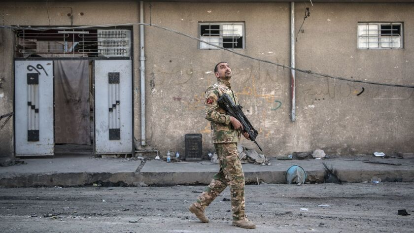 An Iraqi Emergency Response Division soldier looks to the sky after hearing a noise believed to be from an Islamic State drone during fighting in west Mosul on April 7 in Mosul, Iraq.