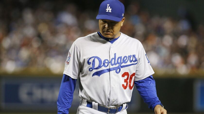 Los Angeles Dodgers manager Dave Roberts walks off the field after pulling his starting pitcher duri
