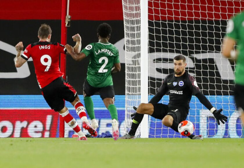 Southampton's Danny Ings, left, scores his team,'s first goal during the English Premier League soccer match between Southampton and Brighton at St. Mary's Stadium in Southampton, England, Thursday, July 16, 2020. (AP Photo/Frank Augstein,Pool)