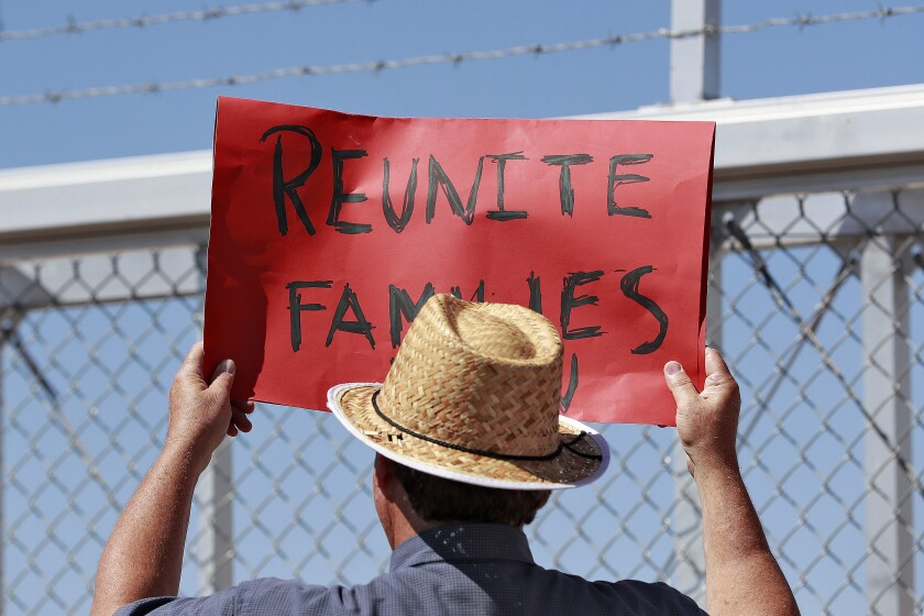 """A protester holds a sign saying """"Reunite Families"""" outside a gate at the Port of Entry facility in Fabens, Texas"""